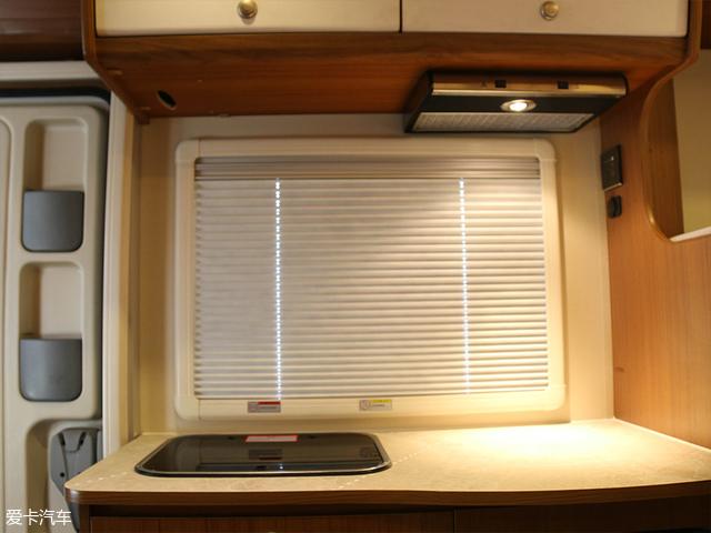 首先介绍这个精致的小厨房,在灶台上方的左侧是一个带玻璃盖的不锈钢水池,水池下方是一个储物区。右侧上方是一个小型吸油烟机,这一侧灶台的下方是一个71L车载房车专用冰箱。