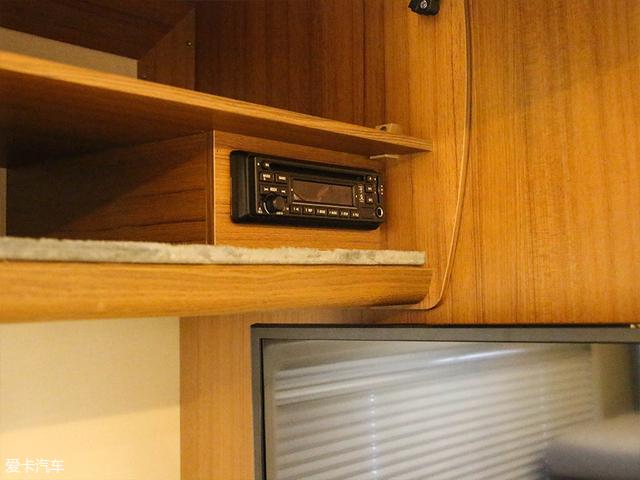 而这款电视的控制器隐藏在其上方的储物柜中,目前仅仅支持CD放映,如果将来可升级成为智能互联电视,效果更佳。
