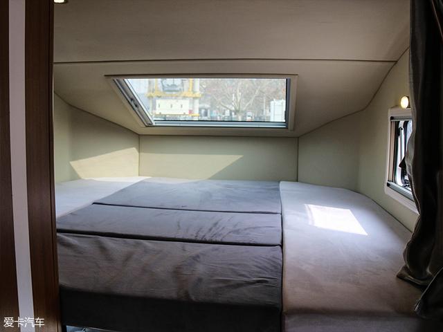 车厢的最前端是一个顶置双人床,这款床的面积为190cm*190cm,我甚至觉得它可以满足四个体型较瘦的人同时在上面休息。而在床铺的两侧设有一个阅读灯和一个双USB接口+220V交流电输入插座。