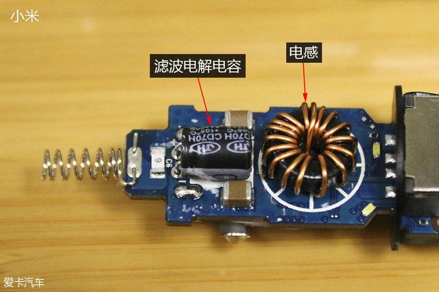"""小米电路板另一侧的主要部件是滤波电解电容与电感。滤波电解电容的主要作用就是提升整个工作电路的稳定性,同时还可吸收电路工作过程中产生的电流波动。值得注意的是,在16款车载充电中我们都发现了它的身影。在滤波电解电容右边的就是电感,它的作用是防止电流变化过大,其通过与电容的合作,可以为用电设备提供最""""干净""""的直流电,减少用电设备损伤。"""