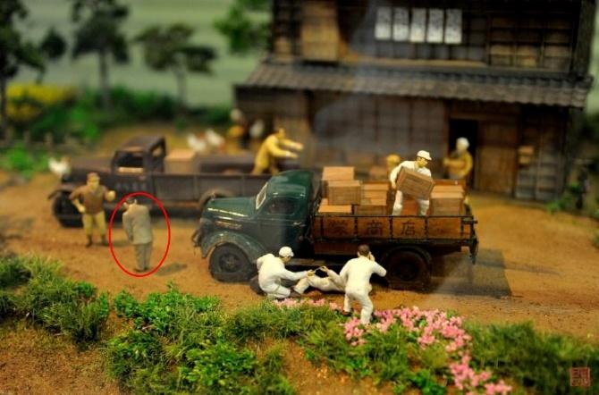"""丰田喜一郎躺在车下修理,虚化背景中,神谷正太郎向客户道歉(图自""""苏雨农""""的博客)"""